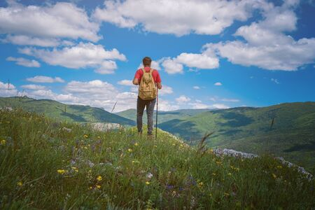 Traveler relaxing meditation with serene view mountains. Travel Lifestyle hiking concept summer vacations outdoor. Happy hiker winning reaching life goal, success, freedom and happiness, achievement