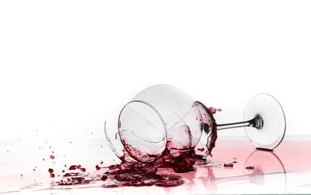 broken wine glass on a quilted table isolated on white background. red wine spills from shards
