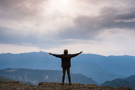 Landscape with silhouette of a standing happy man and raised-up arms on the mountain peak on the background of cloudy sky. autumn rain in the mountains