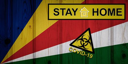 Flag of the Seychelles in original proportions. Quarantine and isolation - Stay at home. flag with biohazard symbol and inscription COVID-19. Stok Fotoğraf