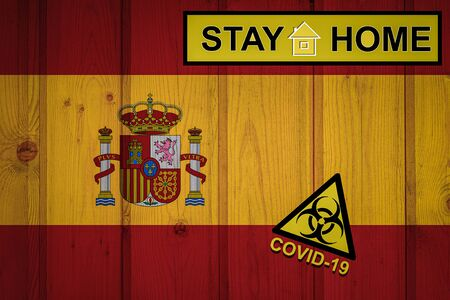 Flag of the spain in original proportions. Quarantine and isolation - Stay at home. flag with biohazard symbol and inscription COVID-19. Stok Fotoğraf