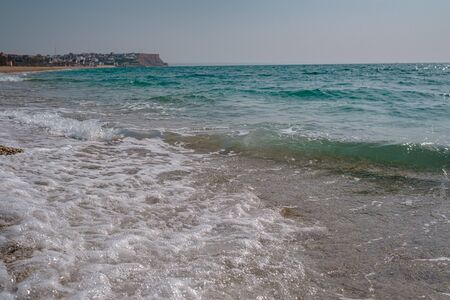 beautiful sea at noon in spring, clear water, rocky beach. silent waves are illuminated by the midday sun