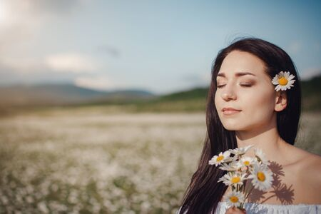 Beautiful young brunette woman in a white dress is enjoying spring in a field of daisies. Health idea and concept, beautiful healthy hair and skin, lack of allergies