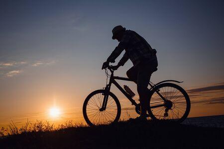 Silhouette eines Hipster-Mannes auf einem Fahrrad auf Sonnenuntergangshintergrund. Idee und Konzept von körperlicher Aktivität und gesundem Lebensstil