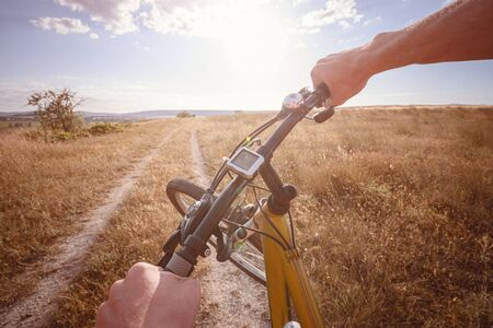 Bike handle bar with lake and sunshine in the background. focus on bike handle bar. picturesque village road at sunset Banque d'images