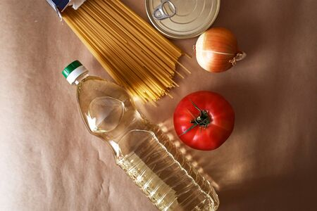 Shopping for products, delivery or donation, food shelf stock for quarantine and lockdown period. Pasta, vegetable oil, canned food, tomato, onion