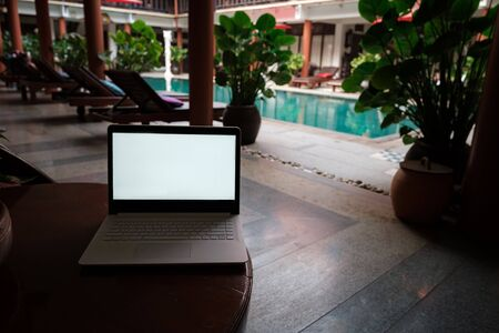 A white laptop on wooden table swiming pool background. A start of new day. Freelance business concept. Flexible remote working, travelling, advert and copy space