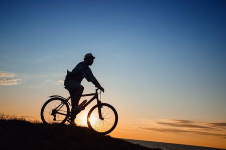 silhouette of a hipster man on a bicycle on sunset background. Idea and concept of physical activity and healthy lifestyle