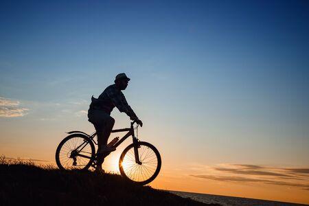 silhouette d'un homme hipster sur un vélo sur fond de coucher de soleil. Idée et concept d'activité physique et de mode de vie sain