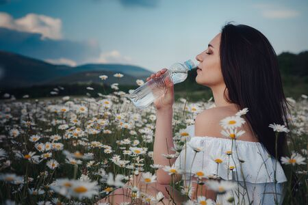 Beautiful young brunette woman in a white dress is enjoying spring in a field of daisies. woman drinking water from a bottle. Health idea and concept, beautiful healthy hair and skin, lack of allergies