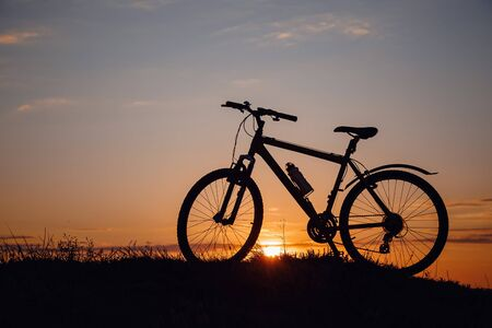 silhouette of a bicycle on the sunset sky. wonderful rural countryside. Weekend in fresh air, among nature.