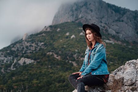 happy asian traveler hipster girl on top of cloudy mountains. stylish woman in hat. atmospheric moment. travel and wanderlust. space for text