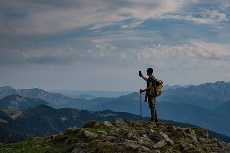 silhouette of Young male hipster in the mountains in autumn take a picture on the smartphone. Discovery Travel Destination Concept. Tourist on the high rocks background. Sport and active life concept.