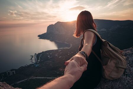 Girl standing on the mountain top over blue sea view. Follow me - POV. Couple enjoying a hike in nature. The concept of the journey to the meeting of new discoveries
