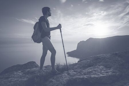 Man hiking at sunset mountains with heavy backpack. Travel Lifestyle wanderlust adventure concept summer vacations outdoor alone into the wild, mock up text. Zdjęcie Seryjne