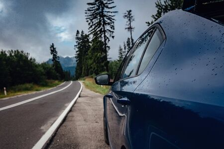 Blue car covered in rain drops for traveling on a mountain road. Mountain road to Lysa Polana and Morskie Oko, High Tatra Mountains, Poland. Free space for your decoration.