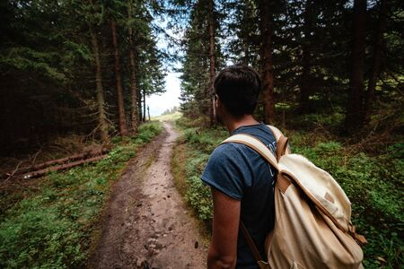 Man hiking at mountains with heavy backpack Travel Lifestyle wanderlust adventure concept summer vacations outdoor alone into the wild. Tatra National Park, Poland
