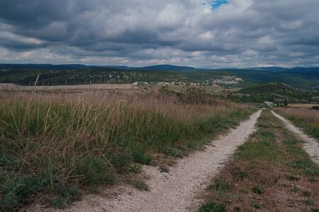 empty dirt road on top of a hill, dramatic sky. idea and concept of travel, open borders and freedom