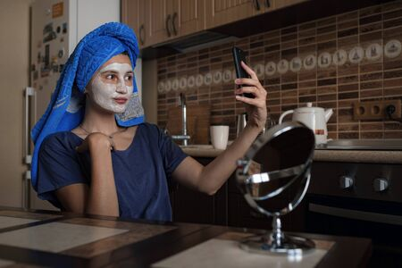 a woman in a blue towel on her head speaks via video link on a smartphone, shoots a vlog . a white clay cosmetic mask on her face. home spa. wellness, morning wake up and body care concept. 写真素材