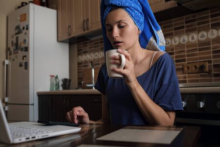 Distance learning online education and work. woman working office work remotely from home on kitchen. Using computer and drinking coffee or tea. Cozy office workplace, remote work, E learning concept Stock fotó