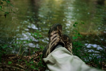legs of a man resting next to a River in forest. Relaxation for legs. Nature and rest concept. Stop and relax while traveling in nature Imagens - 147878966