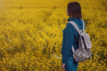 Woman traveler in a blue sweater and jeans in a flowering rapeseed field. Happy beautiful young woman enjoys smell of blooming rapeseed field full of joy and happiness. Concept of freedom