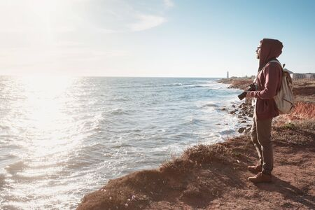 Happy hipster man with backpack standing on the rock and looking at the seashore and beacon at sunset. Hiking in cold season. Wanderlust concept scene.