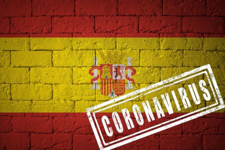 Flag of the Spain with original proportions. stamped of Coronavirus. brick wall texture. Corona virus concept. On the verge of a COVID-19 or 2019-nCoV Pandemic.