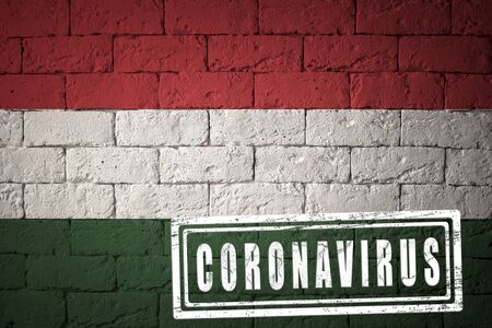 Flag of the Hungary with original proportions. stamped of Coronavirus. brick wall texture. Corona virus concept. On the verge of a COVID-19 or 2019-nCoV Pandemic.