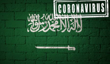Flag of the Saudi Arabia with original proportions. stamped of Coronavirus. brick wall texture. Corona virus concept. On the verge of a COVID-19 or 2019-nCoV Pandemic. Stock Photo