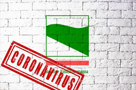 Flag of the regions of Italy Emilia Romagna with original proportions. stamped of Coronavirus. brick wall texture. Corona virus concept. On the verge of a COVID-19 or 2019-nCoV Pandemic. Stock Photo