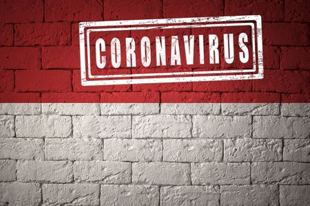 Flag of the Monaco with original proportions. stamped of Coronavirus. brick wall texture. Corona virus concept. On the verge of a COVID-19 or 2019-nCoV Pandemic. Stock Photo