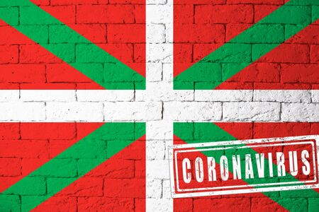 Flag of the regions or communities of Spain Basque Country original proportions. stamped of Coronavirus. brick wall texture. Corona virus concept. On the verge of a COVID-19 or 2019-nCoV Pandemic.