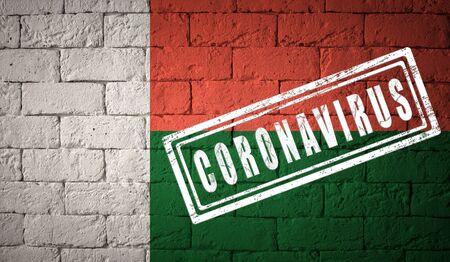 Flag of the Madagascar on brick wall texture. stamped of Coronavirus. Corona virus concept. On the verge of a COVID-19 or 2019-nCoV Pandemic. Novel Coronavirus outbreak