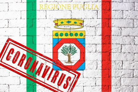 Flag of the regions of Italy Puglia with original proportions. stamped of Coronavirus. brick wall texture. Corona virus concept. On the verge of a COVID-19 or 2019-nCoV Pandemic.