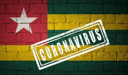 Flag of the Togo on brick wall texture. stamped of Coronavirus. Corona virus concept. On the verge of a COVID-19 or 2019-nCoV Pandemic. Novel Coronavirus outbreak