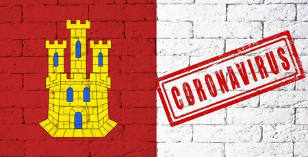 Flag of the regions or communities of Spain Castilla-La Mancha. stamped of Coronavirus. brick wall texture. Corona virus concept. On the verge of a COVID-19 or 2019-nCoV Pandemic.