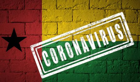 Flag of the Guinea-Bissau on brick wall texture. stamped of Coronavirus. Corona virus concept. On the verge of a COVID-19 or 2019-nCoV Pandemic. Novel Coronavirus outbreak