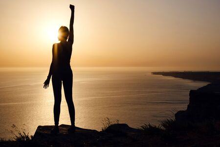 silhouette of woman with raised hands on the beach at sunset. People success, victory, and power. Strong woman, Winning, success , and life goals concept.