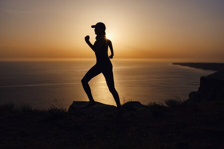 Side view of fitness woman running on a road by the sea. Sportswoman training on seaside promenade at sunset. Summer sport and freedom concept. Athlete training on dusk.
