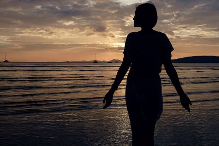 Happy Carefree Woman Enjoying Beautiful Sunset on the Beach. famous Ao Nang beach in Krabi province, Thailand