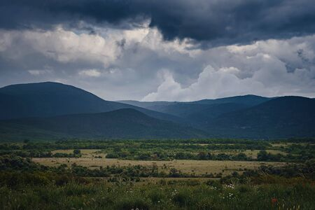 Picturesque green valley among the mountains before a thunderstorm. Dramatic skywith dark clouds and rays of sunshine. Background spring sky.
