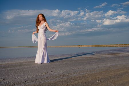 Beautiful young lady with long healthy red hair and cute white dress walking near lake. Hot summer evening. Sunset. Lifestyle concept.