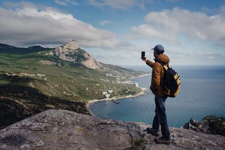 man taking photo of awesome view of mountains with smartphone. travel and discovery concept Banque d'images