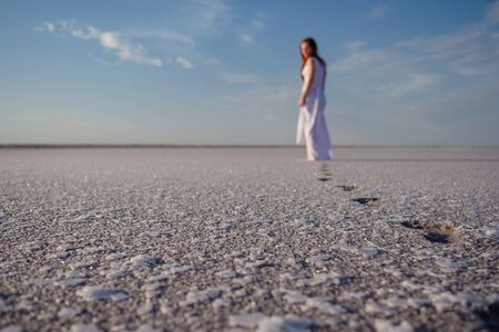Silhouette of young woman walking on Dead Sea at sunrise. Solitude. barefoot prints on salt. lake Sivash
