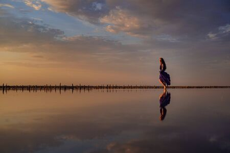 Elegant woman in silky purple dress walking by a salt lake. Romantic mood. Water reflection of clouds and empty space. Holiday, vacation travel scene. glorious sky at sunset Archivio Fotografico