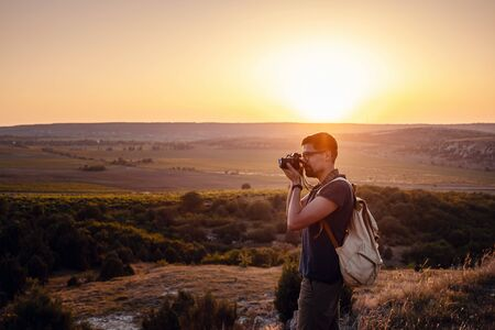Man photographer with backpack and camera taking photo of sunset mountains Travel Lifestyle hobby concept adventure active vacations outdoor 免版税图像