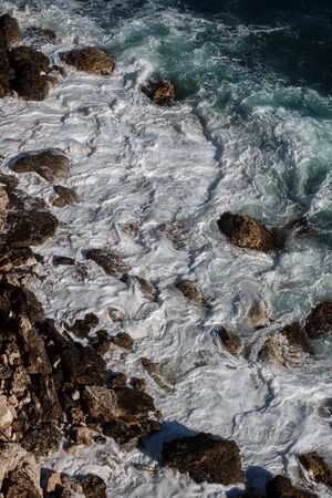 Ocean wave background breaking sea water rocky shore rough seas turquoise water gradient foam. Big waves at open sea. Summer monsoon. White crest of a sea wave. Stok Fotoğraf
