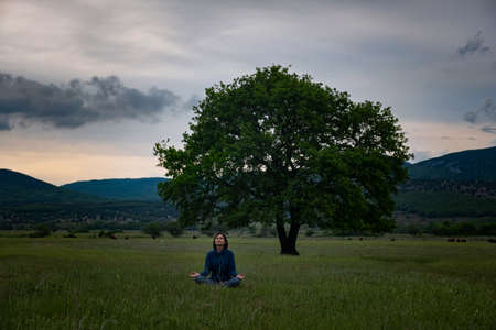 A young woman doing yoga yoga in lotus pose at sunset in the field near bi oak tree. The idea and concept of unity with nature, tranquility and mental health Standard-Bild