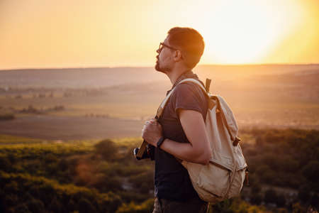Man photographer with backpack and camera taking photo of sunset mountains Travel Lifestyle hobby concept adventure active vacations outdoor Standard-Bild
